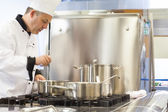 Concentrated head chef stirring in pot — Stock Photo