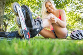 Casual happy blonde tying shoelaces of roller blades — Stock Photo