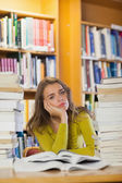 Tired beautiful student studying between piles of books — Photo