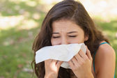 Sick young woman using a handkerchief — Stock Photo