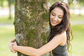 Casual cheerful brunette embracing a tree with closed eyes — Stock Photo