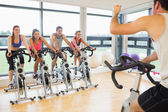 Man teaching spinning class to four people — ストック写真