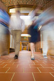 Blurred people walking through open doors — Stock Photo