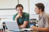Two attractive mature students learning while sitting in class r — Stock Photo