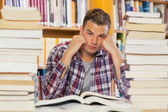 Irritated handsome student studying between piles of books — Stok fotoğraf