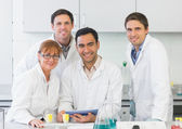 Smiling scientists with tablet PC in the lab — Stock Photo