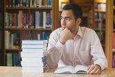 Attractive man sitting in library in front of an opened book — Stock Photo