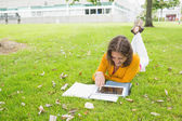 Smiling female student using tablet PC in lawn — Stock Photo