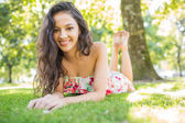 Stylish smiling brunette lying on a lawn looking at camera — Stock Photo