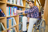 Disabled wheelchair selecting book in library — Stock Photo