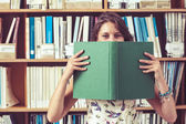 Student holding book in front of her face in library — Stock Photo