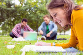 Student writing notes with two using laptop in park — Stock Photo