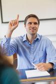 Amused male mature student raising his hand — Stock Photo