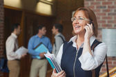 Amused mature student phoning standing in corridor — Stock Photo