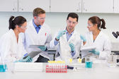 Scientists with tablet PC working on experiment at lab — Stock Photo