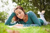 Uśmiechający się dorywczo studentów, leżąc na trawie czytanie książki — Zdjęcie stockowe