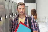 Wesoły przystojny student stojący obok szafki — Zdjęcie stockowe