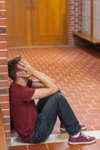 Unhappy handsome student covering his face — Stock Photo