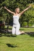 Cheerful young woman jumping in a park — Stock Photo