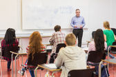Attentive students with teacher in the classroom — Stock Photo