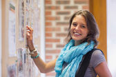 Cheerful student touching notice board — Stock Photo