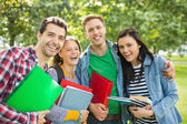Cheerful college students with bags and books in park — Stock Photo