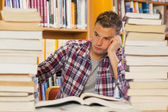 Frustrated handsome student studying between piles of books — Stockfoto
