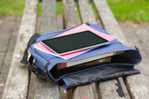 Purple schoolbag lying on park bench — Stock Photo