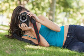 Front view of pretty brunette woman lying on a lawn taking a pic — Stock Photo