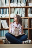 Thoughtful female student against bookshelf with a book — Stock Photo
