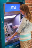 Pretty happy student withdrawing cash — Stock Photo