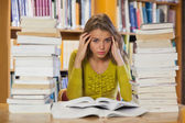 Tired pretty student studying between piles of books — Stock Photo