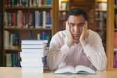 Handsome man sitting in front of an opened book in library — Stock Photo