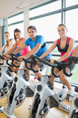 Four people working out at spinning class — 图库照片