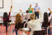 Students raising hands in the classroom — Stock Photo