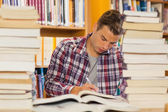 Focused handsome student studying between piles of books — ストック写真