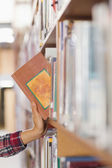 Close up of student taking book out of shelf — Stock Photo