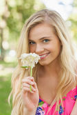 Pretty young woman smelling a white flower — Stock fotografie