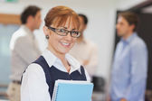 Portrait of female mature student posing in classroom holding so — Stock Photo