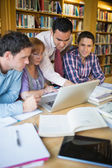 Mature students with teacher and laptop in library — Stock Photo