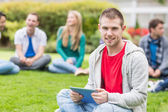 Smiling college boy holding tablet PC with students in park — Stock Photo