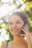 Cheerful young woman calling with her smartphone — Stock Photo