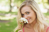Beautiful blonde woman smelling a flower sitting in a park — Stock fotografie