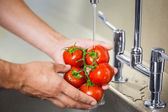 Kitchen porter washing tomatoes under running tap — Stock Photo