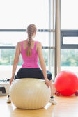 Fit young woman sitting on exercise ball — Stock Photo