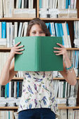Female student holding book in front of her face in library — Stock Photo