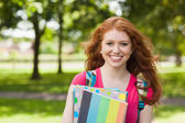 Gorgeous smiling student holding notebooks — Stock Photo