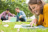 Student using tablet PC while males using laptop in park — ストック写真