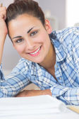 Pretty brunette student smiling at camera while lying on the flo — Stock Photo
