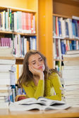 Exhausted beautiful student studying between piles of books — Stock Photo